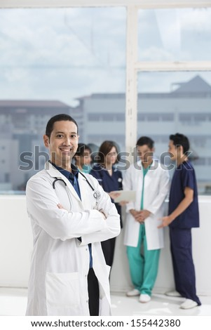 Group of doctors and nurses standing in a hospital. Multi-ethnic team of medical staff. - stock photo