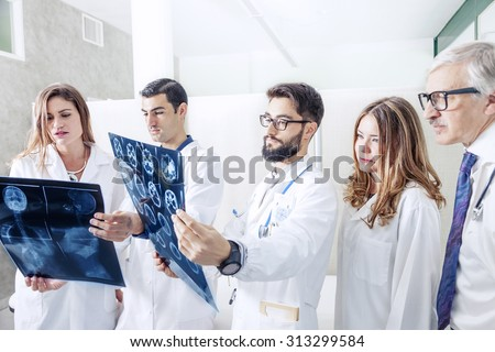 group of doctors examining an x-ray in hospital - stock photo