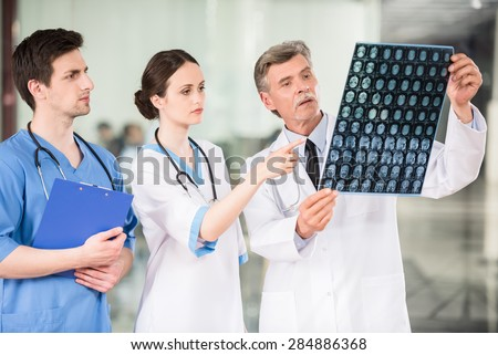 Group of doctors looking at X-ray at offie. - stock photo