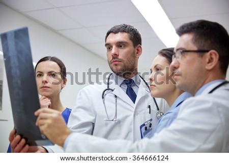 group of doctors looking at x-ray scan image - stock photo