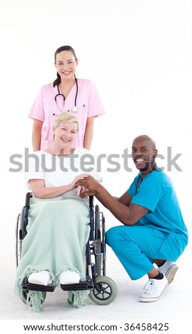 Group of doctors with a patient in a wheel chair smiling at the camera - stock photo
