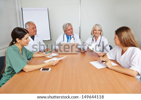Group of doctors with applicant at job interview for a hospital - stock photo