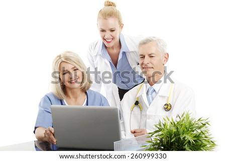 Group of doctors working on laptop while sitting at desk. Isolated on white background. - stock photo