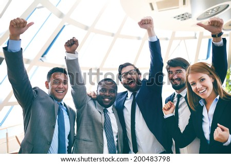 Group of ecstatic business partners looking at camera with raised arms - stock photo