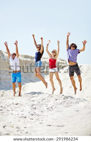 Group of ecstatic friends jumping over sandy beach - stock photo