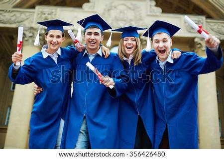 Group of ecstatic graduates with diplomas - stock photo