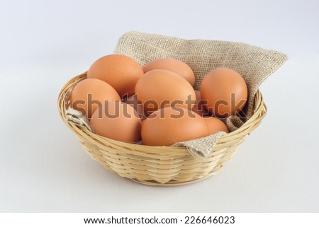 Group of eggs in a straw basket, white background.