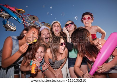 Group of eight female teenagers blowing bubbles together - stock photo