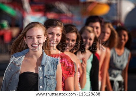 Group of eight girlfriends in a row smiling - stock photo