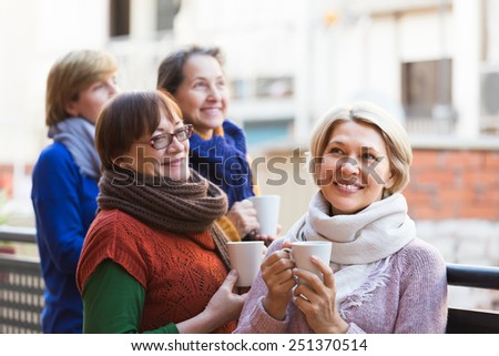 Group of elderly female friends drinking tea at balcony and smiling. Focus on blonde - stock photo