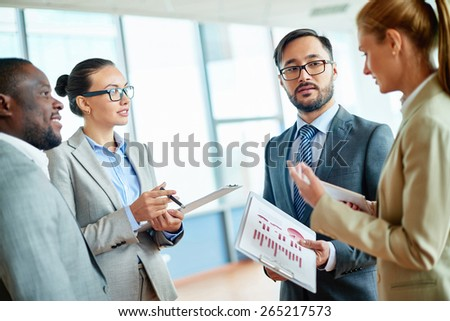 Group of elegant colleagues communicating at meeting