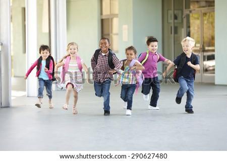 Group Of Elementary Age Schoolchildren Running Outside - stock photo