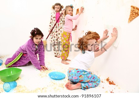 Group of elementary children cleaning up after food fight at slumber party with pizza and popcorn. - stock photo