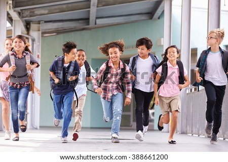 Group of elementary school kids running in a school corridor - stock photo