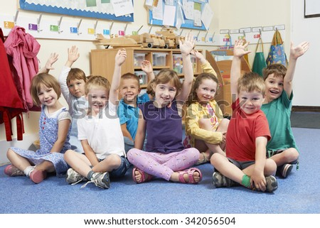 Group Of Elementary School Pupils Putting Hands Up In Class - stock photo