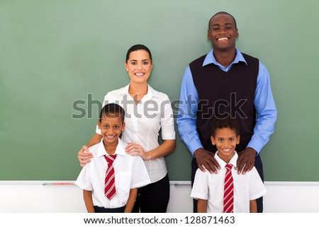 group of elementary school teachers and students in front of chalkboard