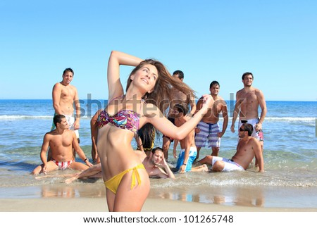 Group of eleven handsome guys on the beach looking at a beautiful girl in bikini - stock photo