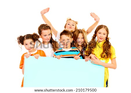 Group of emotional schoolchildren standing together and hold white billboard. Isolated over white. - stock photo