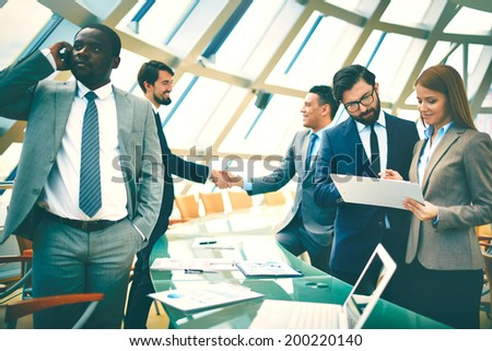Group of employees discussing plan and talking on the phone on background of two businessmen handshaking - stock photo