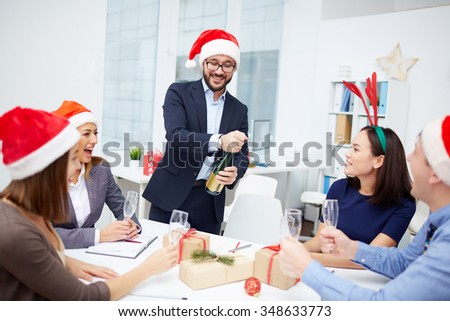 Group of employees looking at their colleague opening bottle of champagne