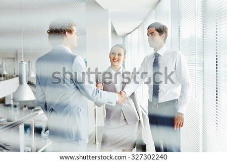 Group of employees talking at meeting in office