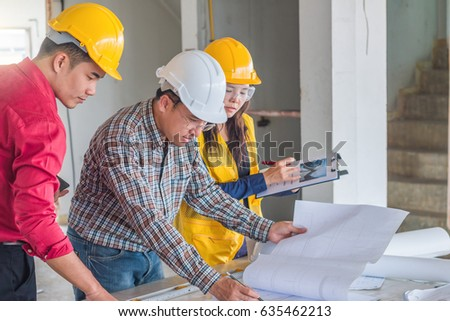 Group engineer checking blueprint on table stock photo 635462213 group of engineer checking the blueprint on the table and talking about construction project with commitment malvernweather Gallery