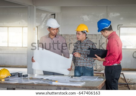 Group engineer checking blueprint on table stock photo 647406163 group of engineer checking the blueprint on the table and talking about construction project with commitment malvernweather Gallery