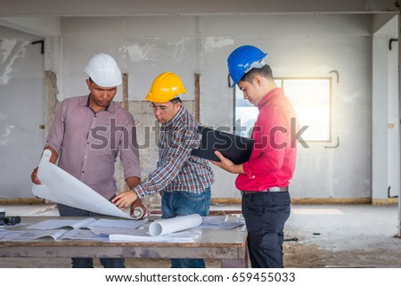 Group engineer checking blueprint on table stock photo 659455033 group of engineer checking the blueprint on the table and talking about construction project with commitment malvernweather Images
