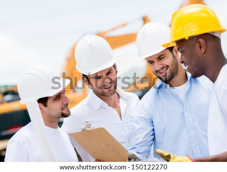 Group of engineers talking at a construction site  - stock photo