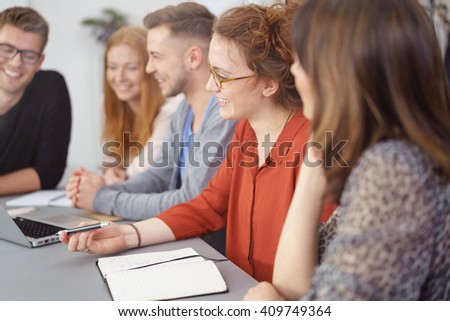 Group of enthusiastic young businesspeople in a meeting working as a team with focus to an attractive smiling young woman in the center viewed in profile - stock photo