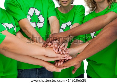 Group of environmental activists putting hands together on white background