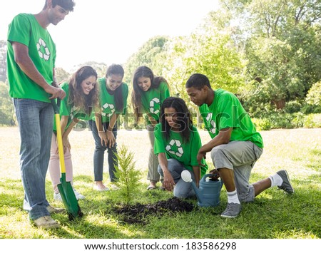 Group of environmentalists looking at plant in park - stock photo