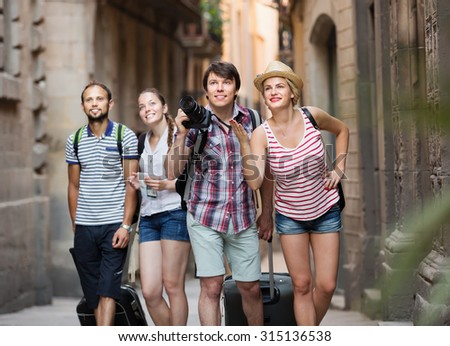 Group of european tourists with camera walking at the street with luggage - stock photo