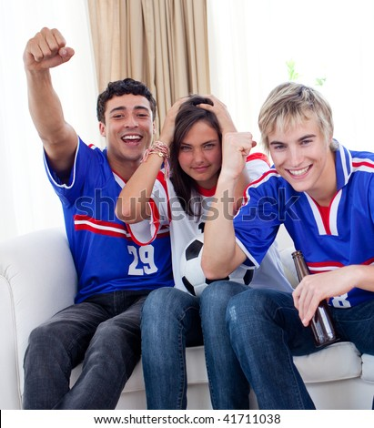 Group of excited and happy adolescents watching a football match at home - stock photo