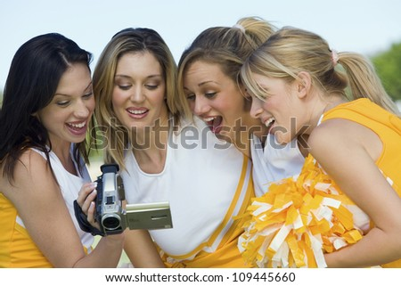 Group of excited cheerleaders watching video on camcorder - stock photo