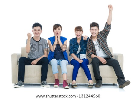 Group of excited friend team on the sofa isolated