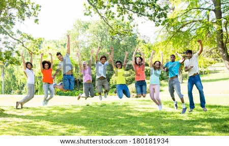 Group of excited multiethnic friends jumping in park - stock photo
