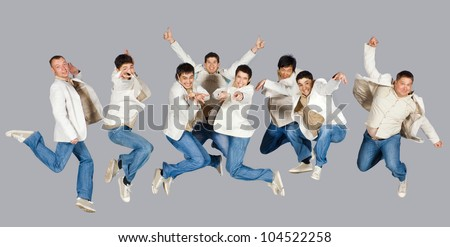 Group of excited people jumping - isolated over gray - stock photo