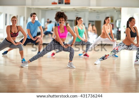 Group of exercisers with female trainer doing exercises for shaping legs and body in gym - stock photo