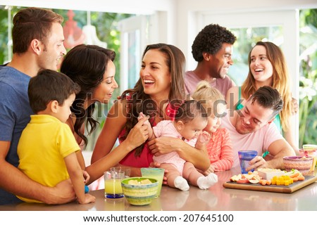 Group Of Families Enjoying Snacks At Home - stock photo