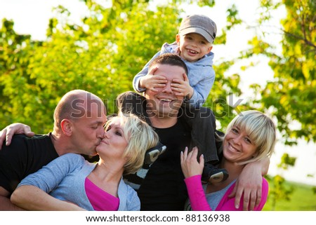 Group of family friends having fun, playing outdoors. Child with parents and a couple kissing - stock photo