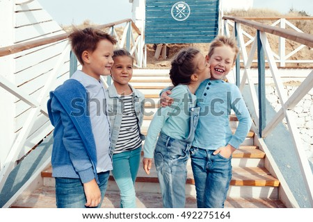 Group of fashion children wearing denim clothing hugging on the sea shore. Autumn casual outfit in blue and navy color. 7-8 years old models.