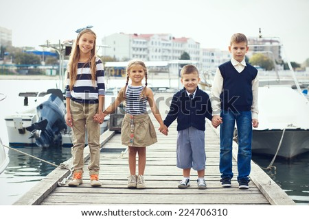 Group of 4 fashion kids wearing navy clothes in marine style posing in the sea port and holding hands - stock photo