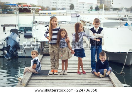 Group of 6 fashion kids wearing same navy clothes in marine style walking in the sea port - stock photo