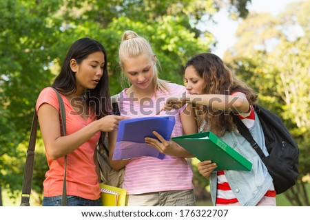 Group of female college friends looking at folder at the campus