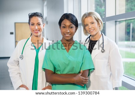 group of female doctors and nurses (Caucasian, African American, Hispanic) smiling in lab coats and scrubs, in hospital looking at camera - stock photo
