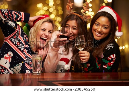 Group Of Female Friends Enjoying Christmas Drinks In Bar - stock photo
