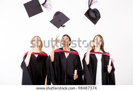 group of female graduates throwing graduation cap - stock photo