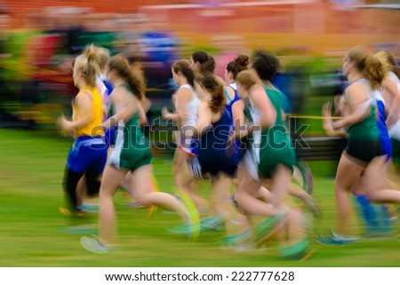 Group of female high school athletes running a cross country race. - stock photo