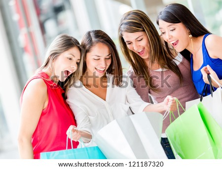 Group of female shoppers looking very excited with their purhcases - stock photo
